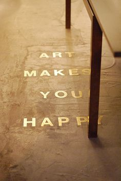 "cement floor with metal letters inlaid ""Art makes you happy"""