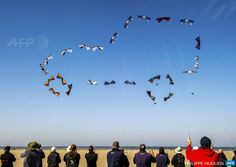 """afp-photo:  FRANCE, Berck : People fly their kites to form the shape of a car in the  sky on the beach in Berck, northern France, on April 20, 2015, during  the 29th """"Rencontres Internationales de Cerfs Volants"""" (International  Kite Meeting) which runs from April 18 to 26. AFP PHOTO / PHILIPPE  HUGUEN"""