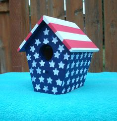 This is a handmade wood bird house that was painted with Acrylic paint. It measures 6.25 inches tall, 5.5 inches wide, and 5.5 inches deep. It is constructed of 1 inch pine board, wood glue, and brads. The roof and floor of the house have been milled down to 1/4 inch. The entrance hole measures 1 1/4 inches. I painted it to resemble the American Flag, with red and white stripes and stars on a navy blue background. This would make a perfect 4th of July gift for the home or garden. It...