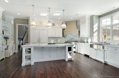 Gorgeous kitchen with gray walls paint color, white kitchen cabinets & kitchen island, marble countertops & slab backsplash, stainless steel apron sink, corner range, pot filler and Restoration Hardware Keynes Prism Single Pendants...