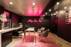 Beautiful office with pink neon, mirrored tile, comfortable chairs and sleek meeting table, black walls, modern desk lamps and custom file cabinet desk. Designed by @gindesigns.