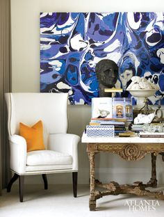 A painting by Kevin Archer hangs above an antique, stone-topped library table that doubles as a dining table when the couple entertains. The wing chair is by Amy Howard.