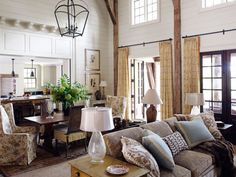 In laying out the interior, architect Stanley Dixon blended a classical sensibility with vernacular mountain style, all in a contemporary vein. The great room's clapboard walls and old barn timbers radiate local charm. Soft golds, browns, and creams knit the living and dining areas with the kitchen. Curtains are G.P. & J. Baker's Poppies.   - HouseBeautiful.com