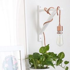 Instead of a traditional table or floor lamp, we love hanging a plug-in vintage Edison bulb on a wall rack. : @sugarandcloth