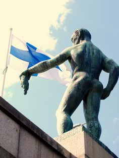 The Finnish national flag flies behind a statue on Hämeensilta bridge, Tampere, on a fine summer's day in Finland.