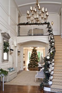 A noble fir is an immediate presence inside this grand entry. Exquisite garland graces the banister.