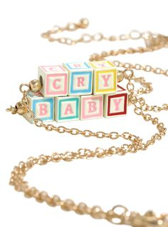 "If they call you cry baby but you don't really care, may as well wear these necklaces and prove them right. The two piece gold tone necklace set from Melanie Martinez has letter blocks that spell out ""Cry"" and ""Baby."" Wear them together as a set or give one to your fellow cry baby bestie. <div><ul><li style=""list-style-position: inside !important; list-style-type: disc !important"">12"" long with 3"" extender</li..."