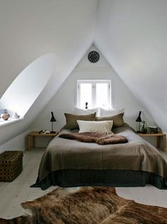 A pretty attic bedroom like this could fit in many little houses. Love the arched window in the slanted ceiling.