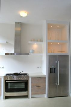 ♥open shelves, white walls and countertops, modern lines...i like the thick frame above the fridge.