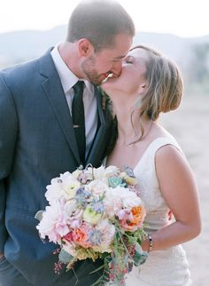 Adorable shot of the bride and groom kissing / laughing | Rustic Chic Wedding Filled With Pretty Pastel Florals | Laura Murray Photography | Bridal Musings