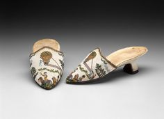 Pair of women's mules. Tops of strung glass beads (called sablé) held together with looping stitches. Pink silk lining, leather soles. Top scene of balloon ascension, with two mounted, uniformed men in foreground, based on print depicting battle of Fleurus of 26 June 1794.