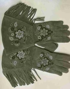 A photograph of a pair of beaded gauntlet style gloves, probably taken in the 1930s or 1940s.