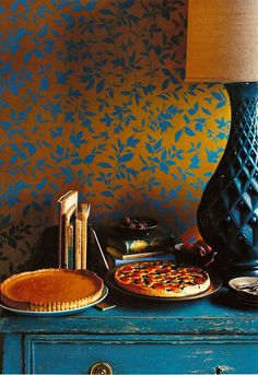 Rich, jewel tones of aqua and orange together.  Love the lamp, the chest, and the wallpaper. . . together they are irresistible.