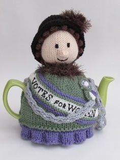 The Suffragette Tea Cosy is a wonderful tribute to the Suffragettes who fought so hard to get equality for women.   The suffragette tea cosy is a well dressed lady wearing a violet dress under a green coat with a fur collar. She has curls peeking from beneath a black hat with a fluffy detailing. As you would expect she has a Votes for Women sash on and is sporting a suffragette rosette.   This votes for women tea cosy is currently on a protest and has chained herself to the teapot. There is…