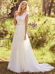 Maggie Sottero - ASHLEY, Lace motifs adorn the bodice and cascade lightly down the tulle skirt of this modest sheath wedding gown, featuring classic cap-sleeves and an elegant V-neckline. Finished with covered buttons over zipper and inner elastic closure. Beaded belt on grosgrain ribbon (Roberta, BB6MS772) sold separately.