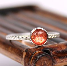The gemstone used for this ring is a 6mm sunstone cabochon. The gemstone is set in a smooth bezel cup made of sterling (925) silver  The ring
