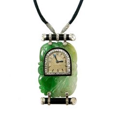 Diamond, Onyx and Jade Pendant Watch, signed Cartier - arch shaped dial with baton and Arabic numerals, blued steel hands, diamond set bezel, inset to a two-tone oblong Chinese carved jade panel, an onyx branch-like baton above and below with rose diamond terminals and rose diamond straps, millegrain set, hung on a black cord with diamond set platinum ends, the case with back-wind movement and numbered 78387 A  Length of pendant 4.8cms /  1 7/8'' ♥≻★≺♥
