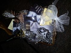 50 Shades gift basket. I put in a bottle of white wine, 2 wine glasses, bubble bath, all 3 books, 50 shades classical music CD, tea, masqurade mask and of course a silver tie.