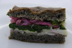 black focaccia with code fish, buttered spinach and lemon marinated onions