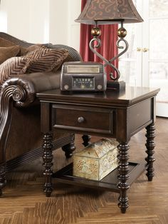 """Ashley Key Town T668-3 Signature Design Rectangular End Table - The rich beauty of the """"Key Town"""" table collection features intricately turned spindle legs, ample drawer space, and  faux woven leather accents, to create traditionally designed pieces that are sure to enhance any living or sitting area."""