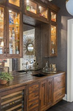 Rustic wet bar features rustic cabinets fitted with a glass-front wine cooler paired with distressed wood countertops fitted with a bar sink and vintage style swing-arm faucet.