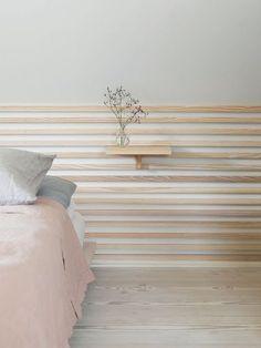 Une tête de lit en tasseaux de bois.