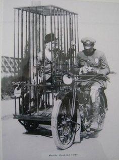 Um policial numa Harley Davidson carregando um prisioneiro na cela móvel - 1921