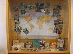 Figure 1:  Many participants in the Flat Stanley Project create physical maps or bulletin boards to track Stanley's travels. This display case at the Middleburg Heights Branch Library shows the pictures, postcards, and souvenirs that accompanied Flat Stanley on his return from different parts of the U.S. and the world. Source: Cuyahoga County Public Library Middleburg Heights Branch.