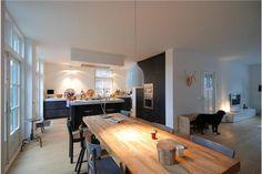 Donkere kastenwand, bij ons in combinatie met houten keukeneiland. Kastenwand contrasteert mooi met de witte omlijsting van de muur.