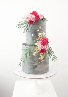 a concrete wedding cake with gold leaf and bold blooms and greenery looks very modern