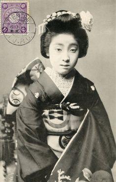 A maiko (apprentice geisha) with the mon (crest) of the Tondaya geisha house in Osaka, wearing bara (rose) hana-kanzashi (flower hairpin). 1910's, Japan. Text and image via Blue Ruin 1 on Flickr