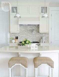 Stunning kitchen features ivory cabinets paired with ivory countertops and stone and glass mosaic tiled backsplash. Ivory kitchen hood with polished nickel, swing-arm pot filler over stainless steel stove across from kitchen island with curved countertop lined with abacus barstools with burlap seats.