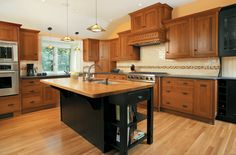 oak kitchen cabinets with dark island | featuring H-legs on base cabinets and custom square legs on island ...