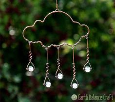 A whimsical copper rain cloud hanging decoration with five blue grey sparkling glass rain drops falling to the ground below. This design is kinetic with dangling droplets that gently swing with movement. This pretty wire decoration loves to be hung in a sunny window for year round