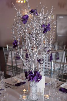 Tall branches in clear vase.  I wouldn't use any flowers.  I would only fill the vase about three inches high with marbles so people can see through to other guests.  May cut beads shorter or even just hot glue individual beads or crystals to branches here and there to dance in the candlelight.