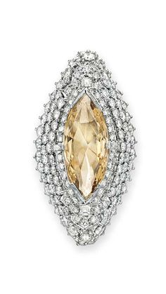 A COLORED DIAMOND AND DIAMOND RING Set with a marquise-cut light brown diamond, weighing approximately 6.27 carats, within a circular-cut diamond navette-shaped surround, mounted in platinum
