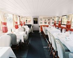 Banquette - Red banquettes and light-gray chairs surrounding square and rectangular dining tables