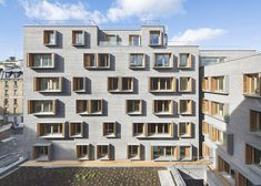 Boxy windows puncture grey brick walls at this Paris development, containing 57 social housing apartments, a hostel and a cinema.