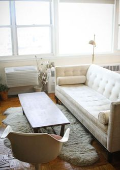 white tufted sofa with rolled pillows <>