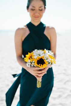 Tampa Wedding - Bridesmaid in navy blue with yellow sunflower bouquet on the beach.    Sophan Theam Photography