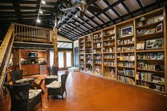 The Barn sits at the back of the property, its sideboards olive green, its stables converted to a screened-in porch. Inside a writing studio with cozy armchairs and floor-to-ceiling bookshelves filled with novels and memoirs and books on the writing craft.    Photo by Edgar Valdes