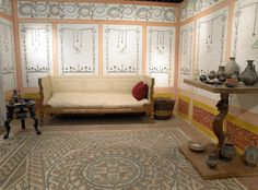 Detail of a reconstructed Roman living room showing the wall paintings which are based on plaster fragments from Austin Friars, the mosaic floor was found in 1869 during the reconstruction of Queen Victoria Street, it is made of various coloured cubes of stone and ceramic. The furniture consists of replicas but all the artifacts come from Roman London.