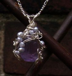 """""""Don't Step on the Mome Raths"""" pendant in silver plate, pearl, and amethyst."""