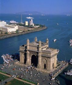The Gateway of India is a monument built during the British Raj in Mumbai City of Maharashtra state in Western India . It is located on the waterfront in the Apollo Bunder area in South Mumbai and overlooks the Arabian Sea.