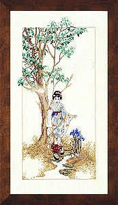 A pretty picture of a lady in traditional dress in a Japanese garden irises and a tree in leaf.