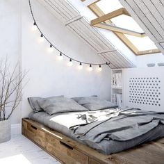 Bed with drawers, pot with branches, big bulb string lights