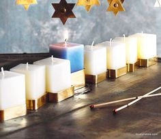 This unique and striking menorah features small square pillar candles set into sleek brass candle cups. The center shamash candle is a subtle shade of blue, the surrounding candles are ivory. Product