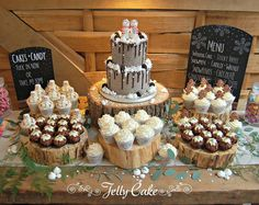 The full dessert table for Chloe and Jay's wedding at Cripps Barn, Bibury. A two tier cake, cupcakes with gingerbread men, snowmen and snowflake decoration and chocolate rice krispie Christmas puds.