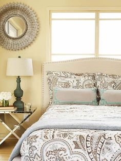 A sunny biscuit hue kicks off this bedroom's comfy neutral color palette. Touches of glam lend a little spark. What we love: Mixing subdude with glam ensures this room is restful but sophisticated. Nailhead trim, a mirrored nighstand, and a gold-tone mirror shine against the warm walls and linen headboard and lampshade. Limiting the pattern to a single oversize paisley on the bedding also keeps in step with the subdued-yet-chic vibe.