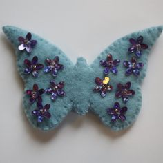These beautiful felt brooch is hand stitched and decorated with metallic purple sequins secured with seed beads. The brooch measures approx by and the brooch fastening is silver plated. This makes a lovely original gift for someone else or. Butterfly Felt, Blue Butterfly, Felt Brooch, Organza Gift Bags, Hand Stitching, Seed Beads, Colours, Purple, Metal